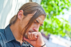 Thoughtful young man. Near the wall of the building Royalty Free Stock Photography