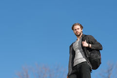 Thoughtful young man against blue sky background with sport bag Stock Photography