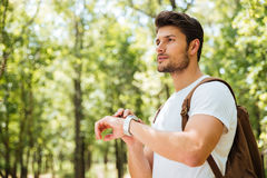 Thoughtful young man with backpack looking at watch in forest. Thoughtful young man with backpack thinking and looking at watch in forest Stock Photography