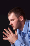 Thoughtful young man in blue shirt Stock Photo