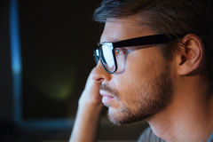 Thoughtful young man with bristle in glasses sitting and thinking Stock Photography