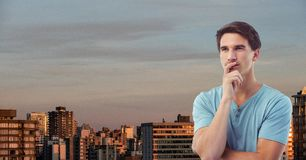 Thoughtful young man in city against sky Stock Photos