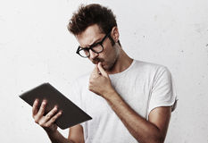 Thoughtful young man with digital tablet Stock Photography
