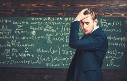 Thoughtful young man in elegant suit standing over green board full of writing. Anxious intelligent professor holding. His hand on head stock photo