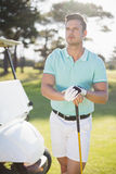 Thoughtful young man with golf club Stock Photo
