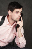 Thoughtful young man with a gun. Young man with a gun in pink shirt  on gray background Royalty Free Stock Photo