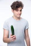Thoughtful young man holding cucumber Stock Image