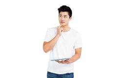 Thoughtful young man holding digital tablet Stock Photo