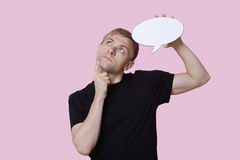 Thoughtful young man holding speech bubble while looking up over pink background Royalty Free Stock Image