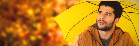 Composite image of thoughtful young man holding yellow umbrella. Thoughtful young man holding yellow umbrella against low angle view of maple leaves Stock Photography