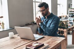 Putting ideas into something real. Thoughtful young man keeping hands clasped while working in the creative working space stock image