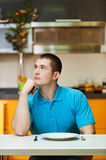 Thoughtful young man in kitchen Stock Image