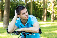 Thoughtful young man leaning on a bicycle Stock Photos