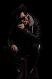 Thoughtful young man in leather jacket sitting on chair Stock Images