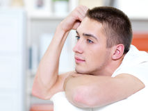 Thoughtful young man lies on a sofa Royalty Free Stock Photo