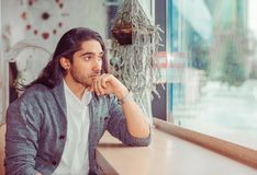 Thoughtful young man in the living room stock images