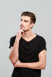 Thoughtful young man looking aside against white background. Thoughtful young handsome man in black t-shirt looking aside against white background Royalty Free Stock Images