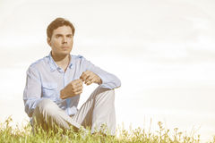 Thoughtful young man looking away while sitting on grass against clear sky Stock Image