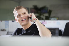 Thoughtful young man looking away while using cell phone at office Royalty Free Stock Photos