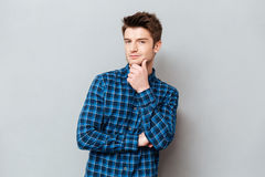Thoughtful young man looking camera with folded hands. Over grey stock photography