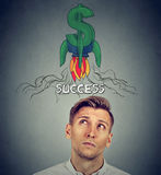 Thoughtful young man looking up at rocket dollar sign above head. Financial business success concept. Thoughtful young man looking up at rocket dollar sign above Stock Photography