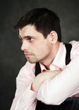 Thoughtful young man in pink shirt. On gray background Stock Photography