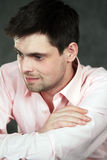 Thoughtful young man in pink shirt. On gray background Stock Photos
