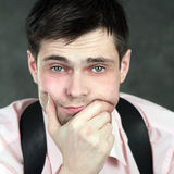 Thoughtful young man in pink shirt. On gray background Royalty Free Stock Photography