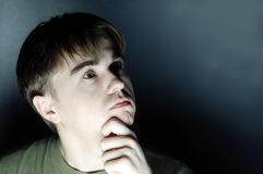 Thoughtful young man portrait in dark background. Man looking away, businessman thinking about future in dark room, serious face Royalty Free Stock Photos