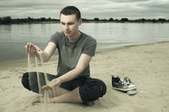 Thoughtful young man sitting on the beach Stock Photos