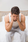 Thoughtful young man sitting in bed Stock Images
