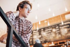 Thoughtful young man is sitting in confectionery shop. She is drinking coffee while waiting for someone.  Stock Photos