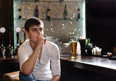 Thoughtful young man sitting thinking in a bar Stock Image