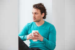 Thoughtful young man sitting on windowsill and drinking coffee Royalty Free Stock Image
