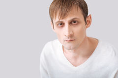 Thoughtful young man standing against the grey background. Fixed gaze. Serious thoughtful young man wearing a white pullover and looking at you while standing Stock Photos