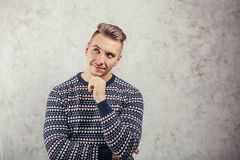 Young man standing near wall and think. Thoughtful young man standing near wall and think royalty free stock photography