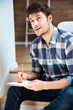 Thoughtful young man thinking and writing in notepad at home Stock Images