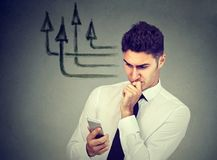 Thoughtful business man using mobile phone texting sending messages. Thoughtful young man using mobile phone texting sending messages making right choices Royalty Free Stock Photography