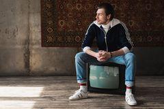 Thoughtful young man in vintage clothes sitting on retro tv set in front of rug hanging. On wall stock photo