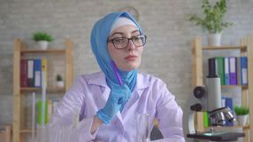 Thoughtful young muslim woman scientist chemist in national scarf working in the lab. Thoughtful young muslim woman scientist chemist in glasses in national stock footage