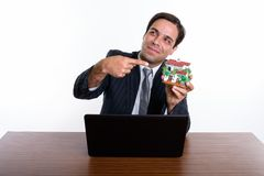 Thoughtful young Persian businessman holding and pointing at hou. Se figurine with laptop on wooden table against white background stock photos