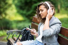 Thoughtful young female student in headphones. Relaxing and listening to music, while drinking coffee in the park. Lifestyle and stock photography