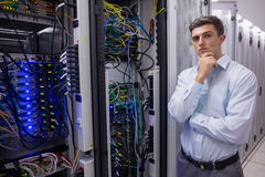Thoughtful young technician with arms crossed Stock Photo