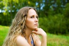 Sad beautiful woman with long curly hairs outdoor Stock Photos