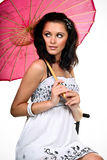 Thoughtful young woman. In white sitting with pink umbrella isolated on white stock images