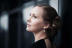 Sad young fashion woman daydreaming at the wall Royalty Free Stock Photography