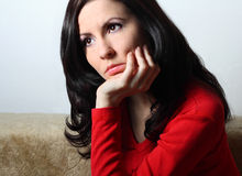 Thoughtful young woman. Young good looking brunette with long hair sitting supporting her head with hand Royalty Free Stock Image