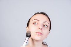 Thoughtful Young Woman Applying Makeup on Face Stock Photo