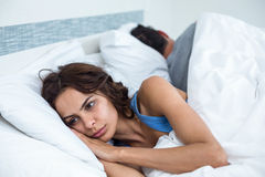 Thoughtful young woman besides husband in background lying on bed Royalty Free Stock Photos