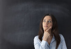 Thoughtful young woman on chalkboard background Royalty Free Stock Image